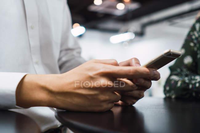 Abgeschnittenes Bild eines Mannes mit Smartphone im Büro — Stockfoto