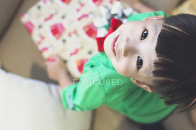 A happy little boy in a green shirt opens his Christmas present — Stock Photo