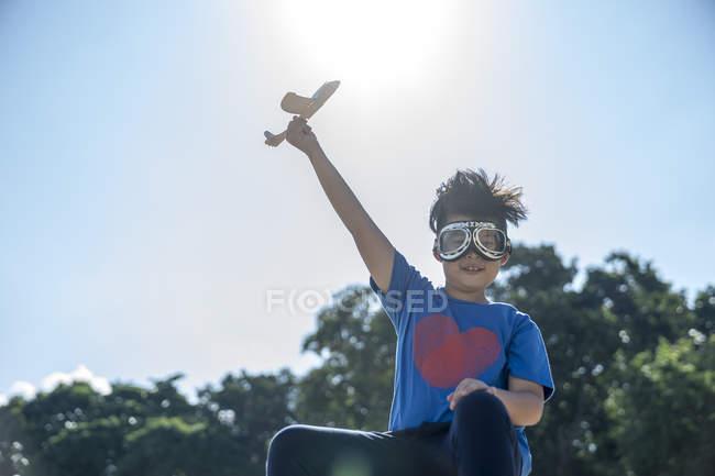 Superhéroe niño jugando con un avión de juguete - foto de stock