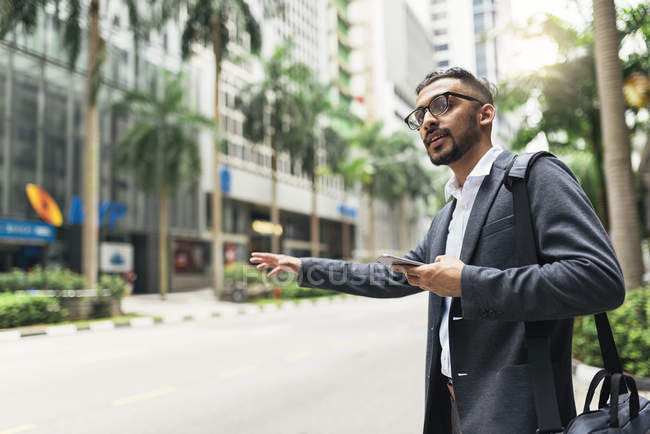 Young successful businessman using smartphone and catching cab — Stock Photo