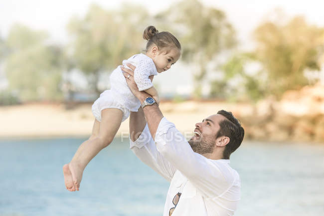 Happy caucasian family on beach, father holding daughter — Stock Photo