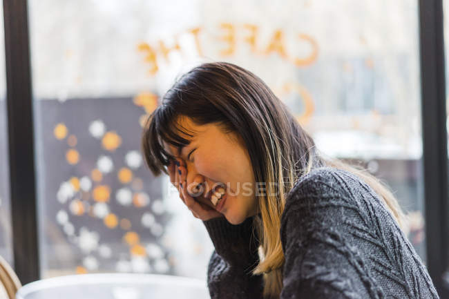 Young attractive casual asian woman laughing in cafe — Stock Photo