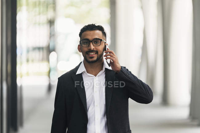 Young successful businessman using smartphone — Stock Photo