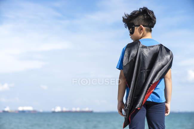 Ragazzo supereroe che controlla il suo lato sinistro, vista posteriore — Foto stock
