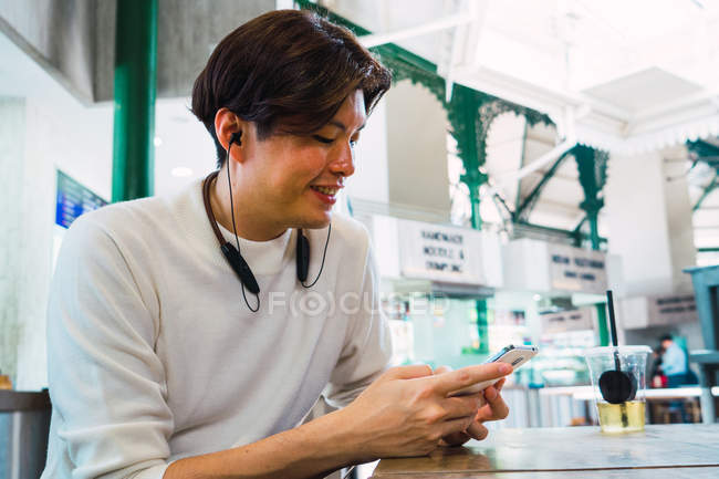 Young asian man using smartphone in cafe — Stock Photo