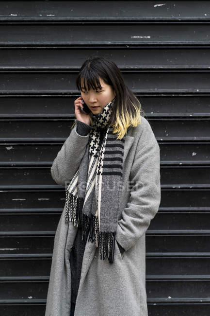 Молодая привлекательная случайная азиатка с помощью смартфона — стоковое фото