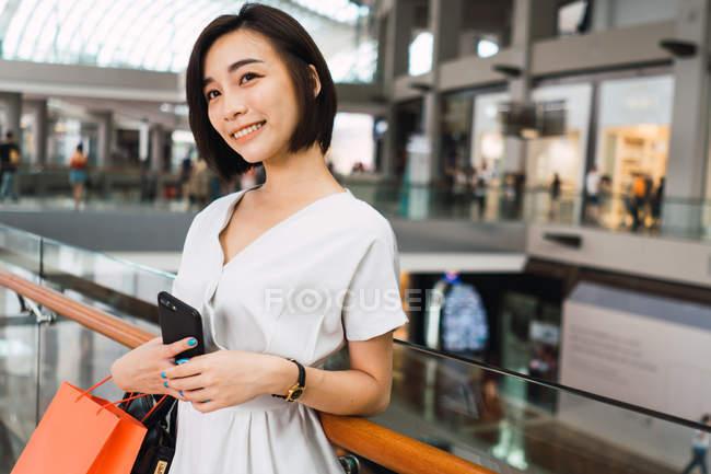 Joven hermosa mujer asiática con bolsas en centro comercial - foto de stock