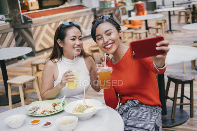 Young asian female friends taking selfie at food court — Stock Photo