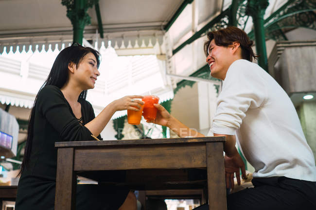 Young asian couple sharing beverages in cafe — Stock Photo