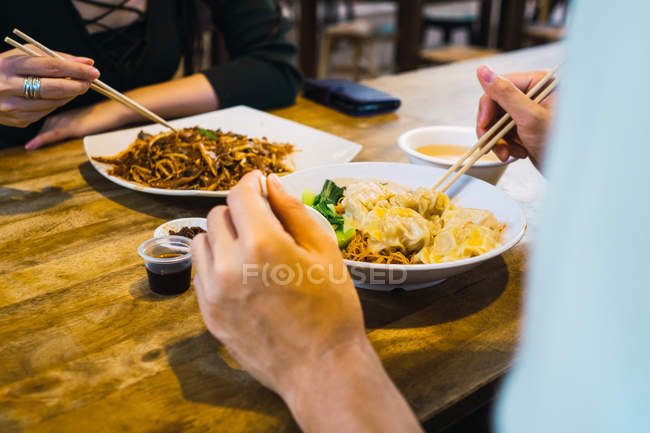 Cropped image of couple eating food in cafe — Stock Photo