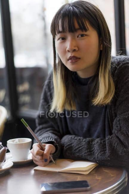 Молодий привабливою випадковий азіатські жінки писати замітки в кафе — стокове фото