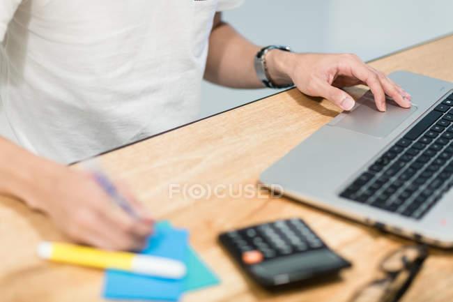 Mann benutzt Laptop in einer Startup-Umgebung. — Stockfoto