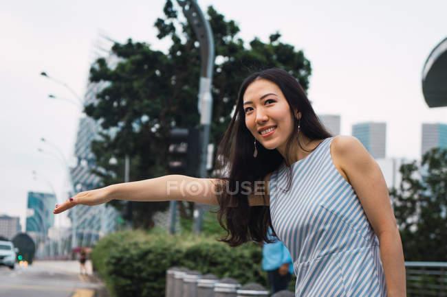 Junge asiatische Frau fängt Taxi auf der Straße — Stockfoto