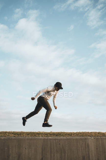 Young Asian man doing parkour against blue sky — Stock Photo