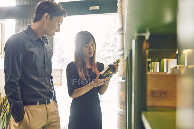 Coppia di giovani amici asiatici insieme scegliendo il vino in negozio — Foto stock