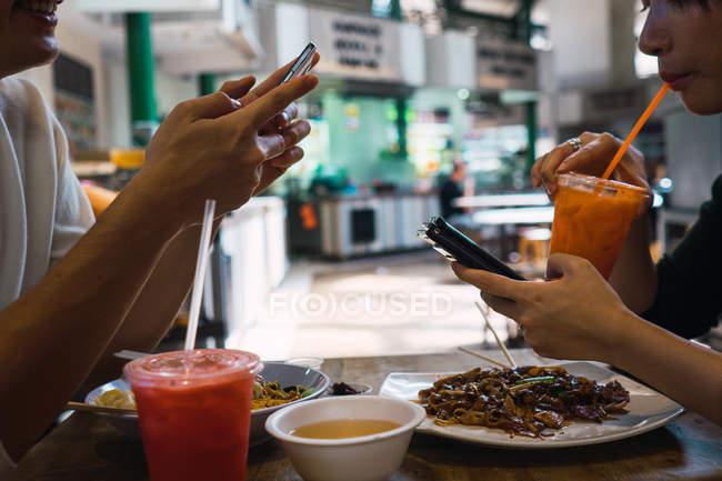 Junge asiatische Paar Essen im Café und Smartphone — Stockfoto