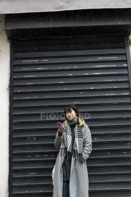 Молодая привлекательная случайная азиатка с помощью смартфона на улице — стоковое фото