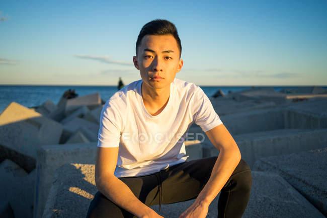 Retrato de joven asiático hombre sentado y mirando a la cámara - foto de stock