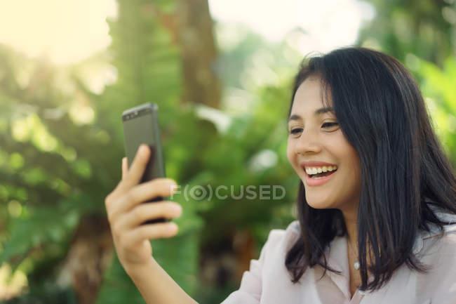 Heureuse femme asiatique qui se selfie dans parc — Photo de stock