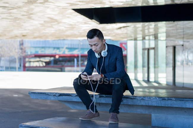 Jovem asiático homem usando smartphone na cidade — Fotografia de Stock