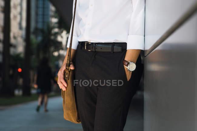 Обрезанный образ успешного молодого бизнесмена, стоящего у стены — стоковое фото