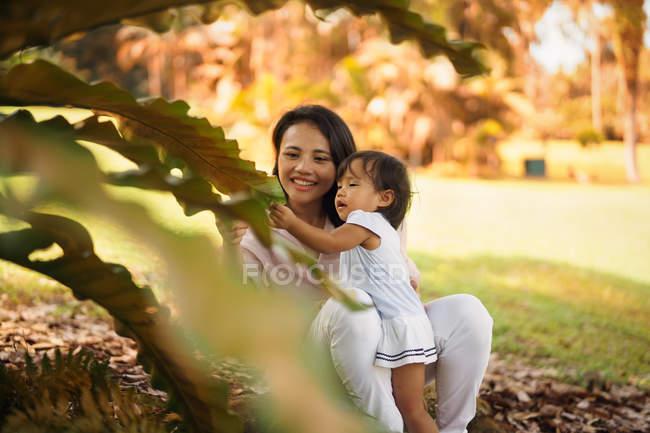 Linda asiática madre e hija que se divierten en el Parque - foto de stock