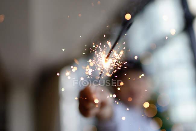 Vue rapprochée du feu d'artifice scintillant dans la main du garçon, mise au point sélective — Photo de stock