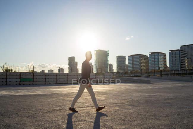 Vista lateral de jovem asiático homem andando na cidade ao pôr do sol — Fotografia de Stock