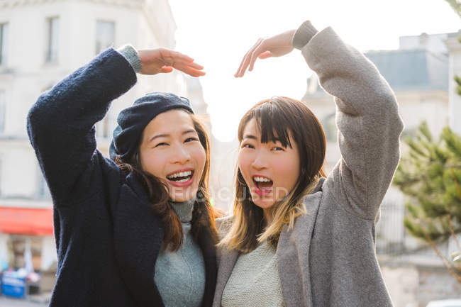 Young adult asian female friends with hands forming heart shape — Stock Photo