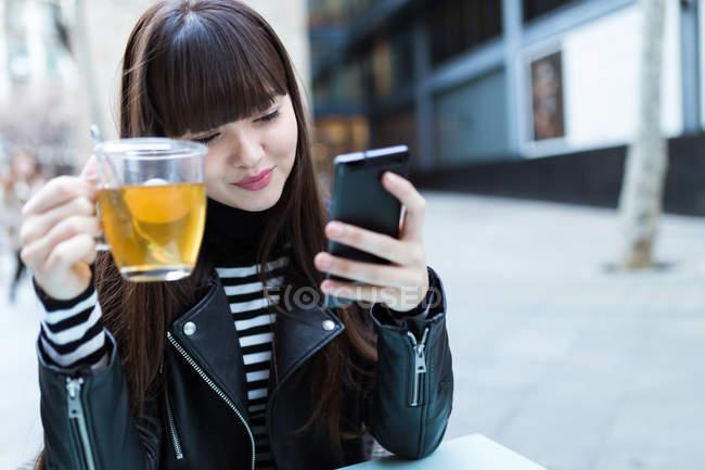 Mujeres de pelo largo mirando su teléfono inteligente - foto de stock