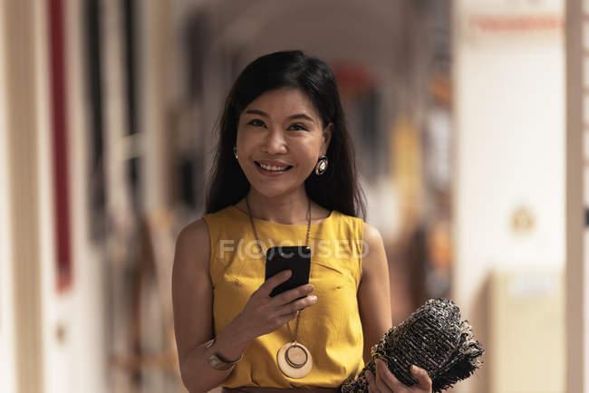 Feliz joven asiático mujer usando smartphone - foto de stock