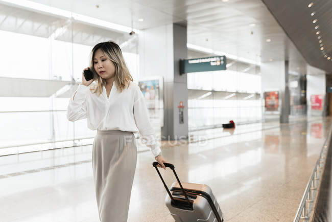 Young successful businesswoman with smartphone in airport — Stock Photo