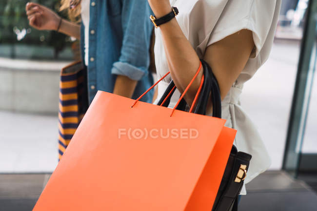 Cropped image of women with shopping bags — Stock Photo