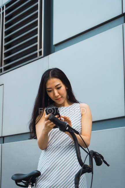 Young asian woman with bike using smartphone — Stock Photo