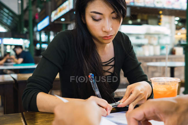 Jeune asiatique femme écriture quelque chose à table — Photo de stock