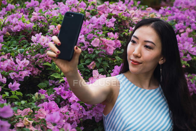 Young asian woman taking selfie with flowers — Stock Photo