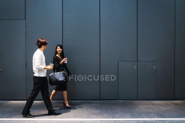 Молодая азиатская пара, выходящая на улицу с напитком — стоковое фото