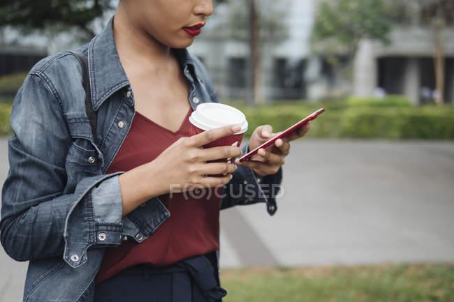 Ritratti di una giovane signora di Singaporean Malese usando il suo telefono in un ambiente urbano per le strade di Singapore — Foto stock