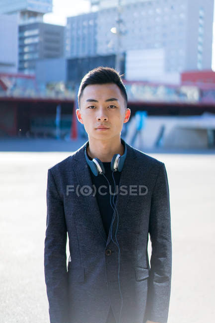 Portrait of young asian man in suit and headset — Stock Photo
