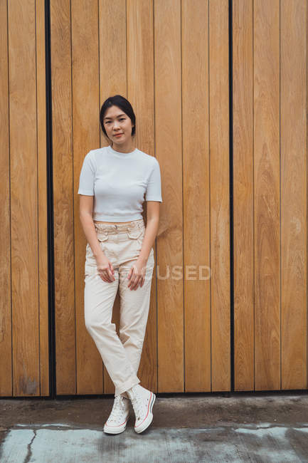 Young attractive asian woman standing against wooden wall — Stock Photo