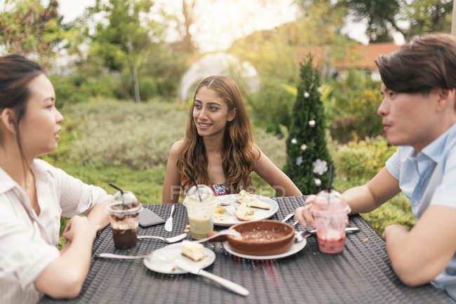 Группа друзей в ресторане, говоря сидя за столом — стоковое фото