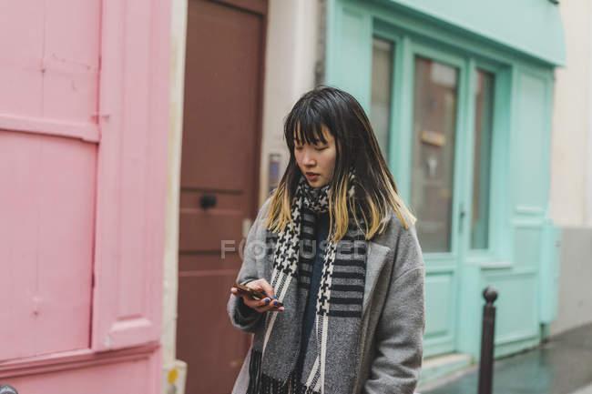 Jovem atraente casual mulher asiática usando smartphone na rua — Fotografia de Stock