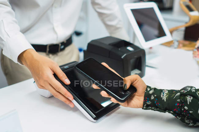 Cropped image of people sharing with wireless devices — Stock Photo