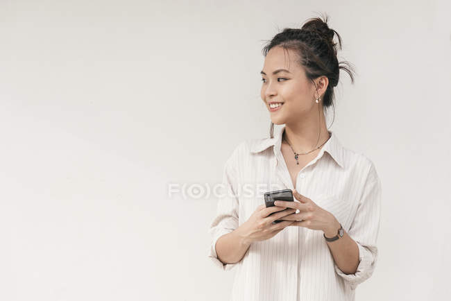 Young asian woman with smile using smartphone — Stock Photo