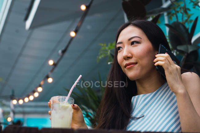 Young asian woman with drink and smartphone — Stock Photo