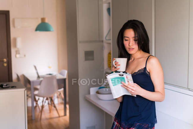 Young chinese woman reading a magazine with a cup of coffee at home — Stock Photo