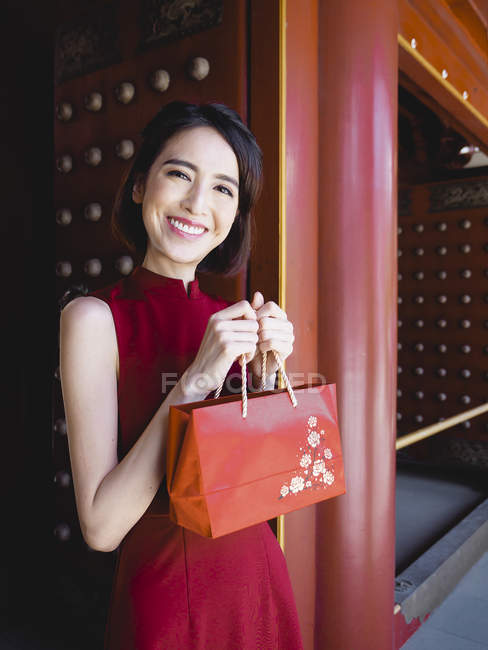 Chinese woman with red purse looking at  camera — Stock Photo