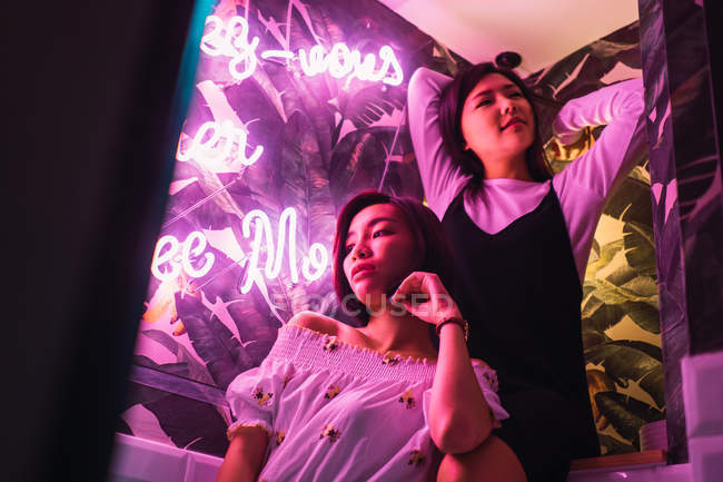 Young asian women posing for photo in comfortable bar — Stock Photo