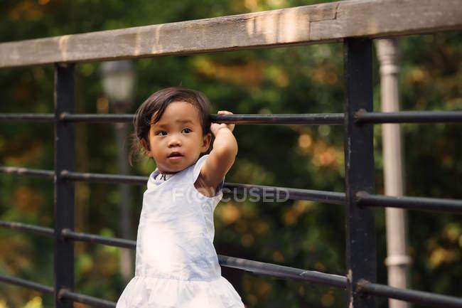 Cute little girl standing beside fence in park — Stock Photo
