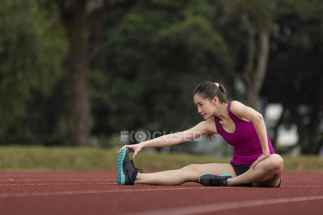 Молодая азиатка растягивается на гоночной трассе в плохую погоду. Она готовится к ежедневным упражнениям, несмотря на погоду. . — стоковое фото